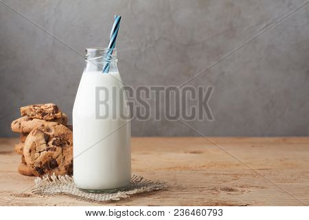 Bottle With Milk And Chocolate Chip Cookies On Dark Background With Copy Space.