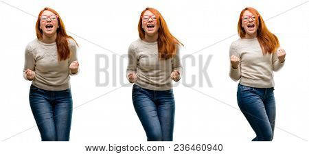 Young Beautiful redhead woman happy and excited celebrating victory expressing big success, power, energy and positive emotions. Celebrates new job joyful