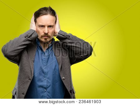 Handsome young man covering ears ignoring annoying loud noise, plugs ears to avoid hearing sound. Noisy music is a problem.