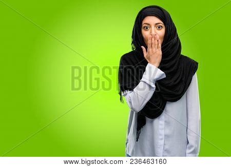 Young arab woman wearing hijab covers mouth in shock, looks shy, expressing silence and mistake concepts, scared