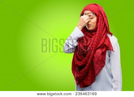 Young arab woman wearing hijab with sleepy expression, being overworked and tired, rubbes nose because of weariness