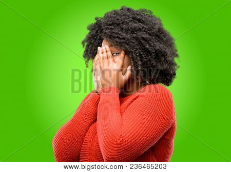 Beautiful african woman smiling having shy look peeking through her fingers, covering face with hands looking confusedly broadly