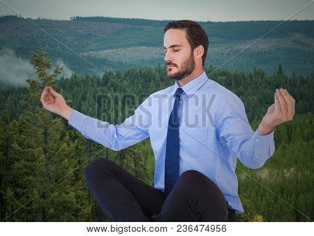 Business man meditating against trees on hills