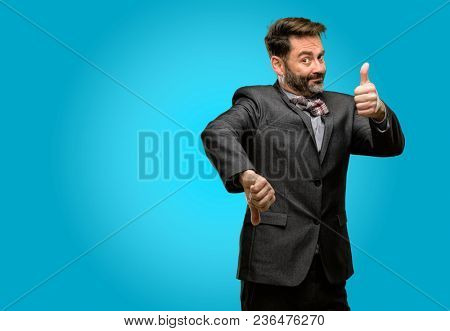 Middle age man, with beard and bow tie confused with thumbs up and down, trying to take a decision expressing doubt and frustration
