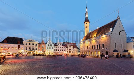 TALLINN, ESTONIA - JULY 30, 2017: People on the Town Hall square in the night. The Old Town is one of the best preserved medieval cities in Europe and is listed as a UNESCO World Heritage Site