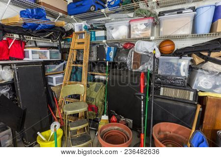 Messy residential garage packed full of boxes, tools and gardening items.