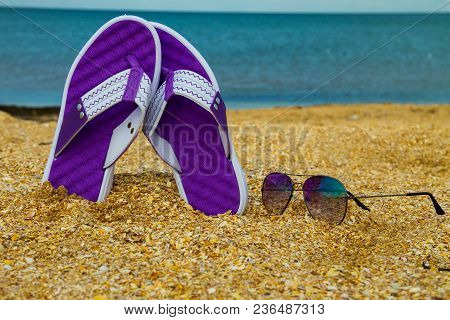 Pair Of Flip Flops And Sunglasses On A Sandy Sea Beach. Summer Vacation Concept