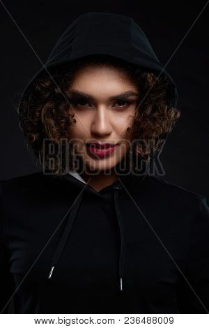 Curly Girl Wearing Black Sport Hood Looking At Camera. Looking Confident And Charismatic. Model Havi