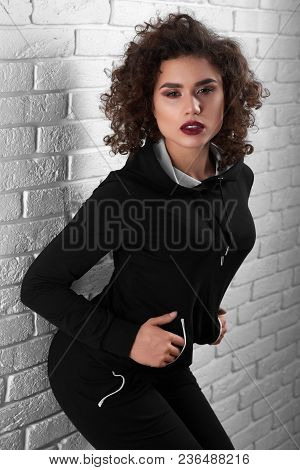 Sexy Curly Exotic Girl Posing Near White Wall. Model Having Beatiful Young Face, Intresting Hairstyl