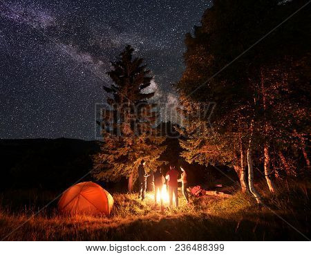 Group Of Four Friends Hikers Warming Their Hands Around A Campfire, Having A Rest Near Glowing Orang