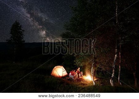 Four Friends Tourists Having A Rest By The Campfire, Sitting On Logs During Night Camping Among Tree