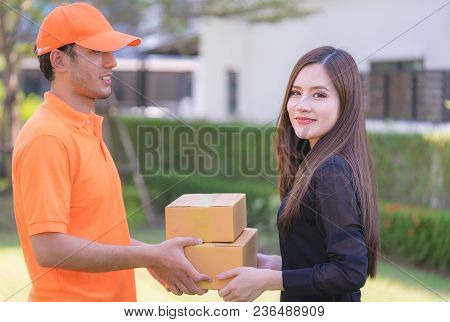 Happy Woman Is Receiving Package From Delivery Man