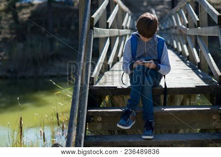 Young boy using smart phone at the river bank. Cute 11 years old boy sitting on wooden bridge at spring park. Kid's outdoor portrait.
