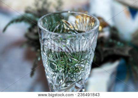 The Top Part Of The Crystal Glass With A Pattern Stands On A Table With A Blurry Background In The F