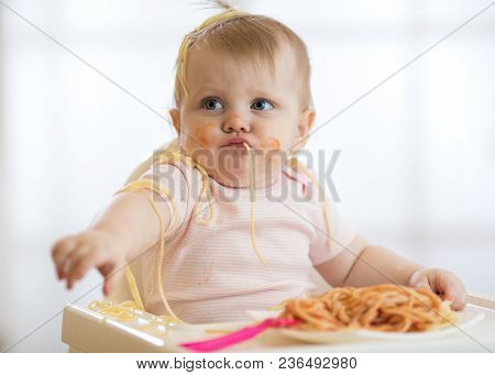 Adorable Little Baby One Year Old Eating Pasta Indoor. Funny Toddler Child With Spaghetti. Cute Kid