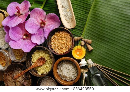 Different salt in wooden bowl,candle, oil orchid on banana leaf