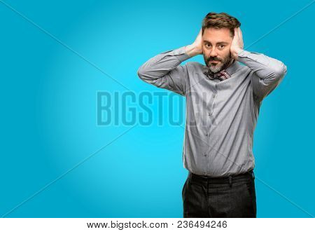 Middle age man, with beard and bow tie covering ears ignoring annoying loud noise, plugs ears to avoid hearing sound. Noisy music is a problem.