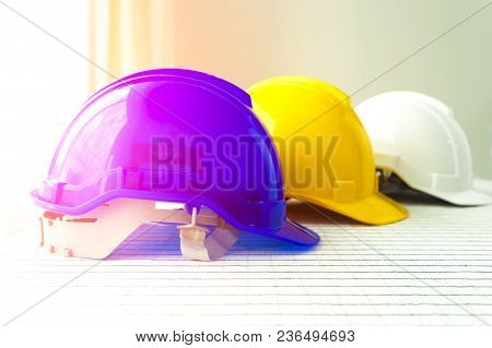 The Blue, Yellow And White Safety Helmet Stacking On Table With The Blueprint And Measuring Tools At