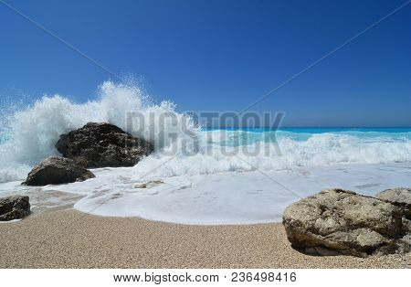 Famous Kathisma Pebble Beach, Clean Turquoise Water, Clear Blue Sky, Strong Sunlight And Big Wave Sp