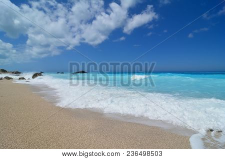 Beautiful Seascape, Idilic Peble Beach, Perfect Turqouise Water, Roling Waves And Blue Sky With Some