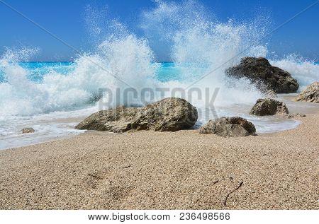 Turquoise Water, Blue Sky, White Splash And Waves Crashing Over Group Of Stones On Popular Kathisma