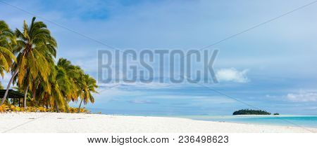 Panorama of stunning tropical Aitutaki One Foot island with palm trees, white sand, turquoise ocean water and blue sky at Cook Islands, South Pacific