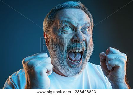 Screaming, Hate, Rage. Crying Emotional Angry Man Screaming In Colorful Bright Lights At Studio Back