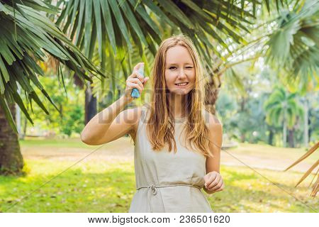 Woman Spraying Insect Repellent On Skin Outdoor.