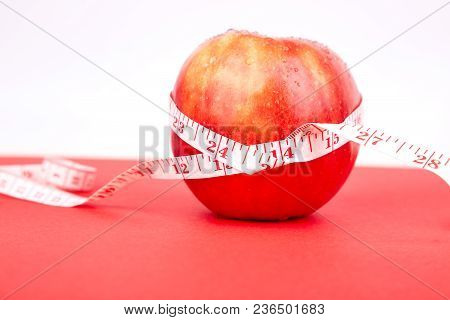 Measuring Tape Wrapped Around A Red Apple