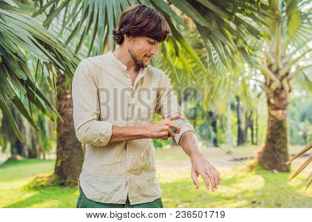 Young man spraying mosquito insect repellent in the forrest, insect protection. poster