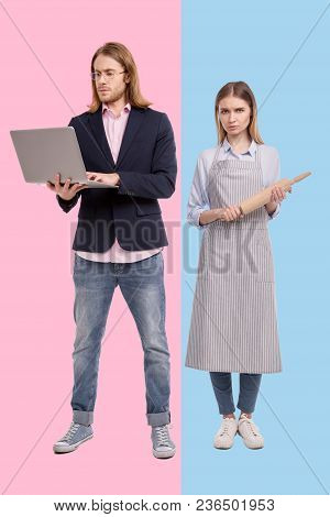 Gender Stereotype. Charming Young Woman In An Apron Posing With A Rolling Pin And Looking Disappoint