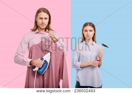 Ruining stereotypes. Handsome young man ironing a shirt and his girlfriend posing with a hammer while posing against pink and blue backgrounds poster