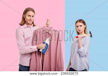Daily Chores. Upbeat Young Man Ironing A Pink Shirt And Smiling At The Camera While His Girlfriend P