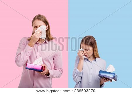 Bitter Tears. Sad Young Couple Crying And Wiping Tears With Tissues While Posing Against Blue And Pi