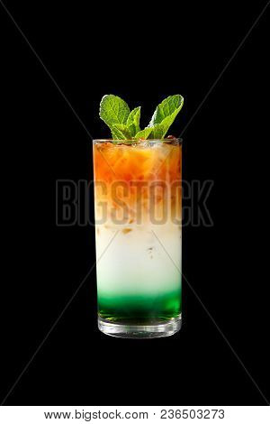 A Multicolored, Three-layered Opaque Cocktail In A Tall Glass With Crushed Ice And Mint Leaves And C