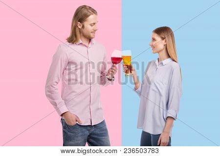 Divergent Taste Preferences. Pleasant Young Woman Holding A Glass Of Beer And Clinking Glasses With