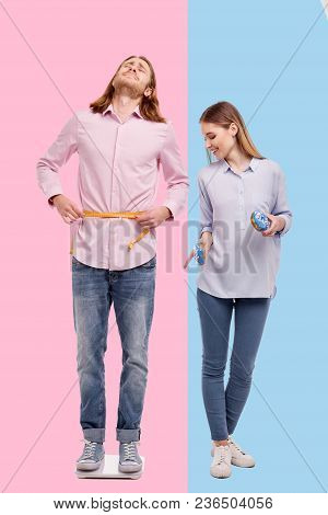 Mocking Laughter. Pretty Slim Woman Holding Doughnuts And Pointing At The Scale With A Mocking Smile