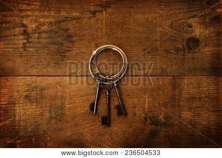 Three old keys on a large ring hanging or hooked to a grungy old wooden wall. Security, Encryption abstract