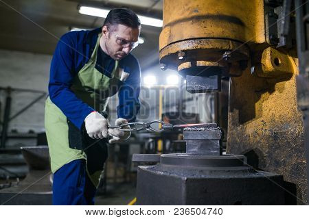 A Man Works In A Smithy. Works On A Pneumatic Hammer, Forges Iron