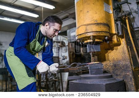 A Brutal Man Works In A Workshop, Forges Iron.