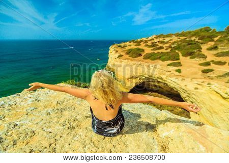 Freedom Blonde Lifestyle Tourist On Cliffs In Algarve Coast Near Lagoa, Portugal. Caucasian Woman Lo
