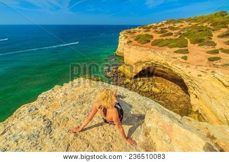 Lifestyle Tourist Sitting On Cliffs In Algarve Coast Famous For Its Rock Formations. Benagil Cave, P