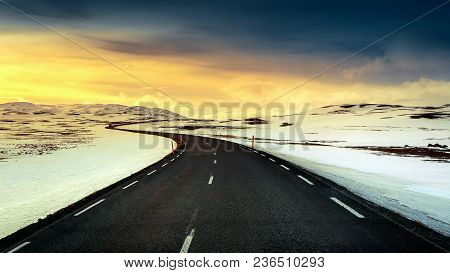 A Long Straight Road At Sunset In Winter.