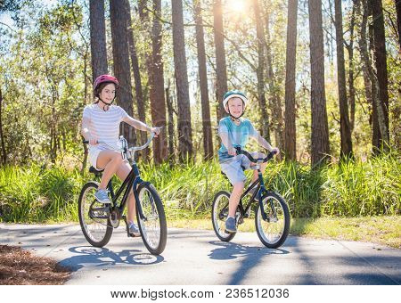 Two kids enjoying a fun bicycle ride together on a bike path in a green forest outdoors. Smiling and enjoying nature on a sunny warm day. Exercising and being active during the summer
