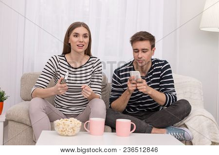 Interesting Film. Pretty Excited Woman Watching A Film And Her Boyfriend Typing On His Phone