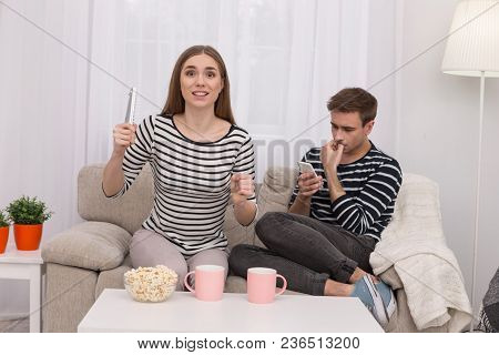 My Favourite Film. Exuberant Excited Woman Watching A Film And Her Boyfriend Typing On His Phone