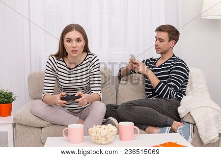 Concentration. Serious Inspired Woman Playing A Game And Her Boyfriend Talking On The Phone