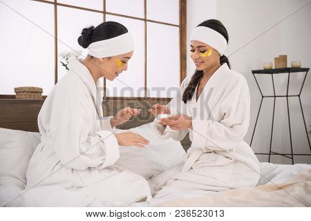 Skin Moisturizer. Nice Young Woman Holding A Bottle With Cream While Testing It Together With Her Gi