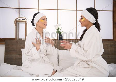 Perfect Skin. Joyful Young Women Sitting Together On The Bed While Trying New Cream