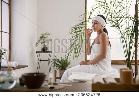 Wonderful Smell. Delighted Young Woman Holding Aroma Oil While Enjoying It Smell